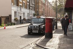 Black taxi cab is on the street of London. London, United Kingdom - October 30, 2017: Black taxi cab by The London Taxi Company stands on the street royalty free stock image