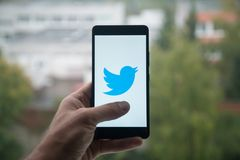 Man holding smartphone with Twitter logo with the finger on the screen. London, United Kingdom, october 3, 2017: Man holding smartphone with Twitter logo with stock photography