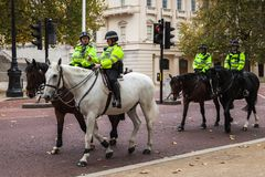 Mounted police ride the street in London. London, United Kingdom - October 29, 2017: Mounted police officers ride the street in London royalty free stock images
