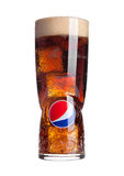 LONDON,UNITED KINGDOM-OCTOBER 03, 2016: Original large glass with pepsi cola and ice cubes and foam isolated on white. Pepsi is a Stock Image