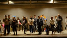 London, United Kingdom - October 20, 2017: Smooth slow motion slider camera shot of people standing and waiting for underground tr stock video