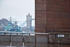 London, United Kingdom - October 7th, 2006: No 1 London Bridge b. Uilding, with HMS Belfast and Tower Bridge over river Thames in background, shot on rainy royalty free stock photo