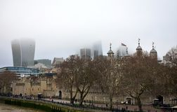 The Tower of London and The City with mist from Tower Bridge. Skyscrapers with fog and Thames River walk. London, UK, 30 Dec 2018. royalty free stock photo