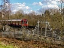 London-Untertagezug, der vorbei auf Bahn in Chorleywood überschreitet lizenzfreie stockfotografie