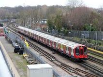 London-Untertagezug, der vorbei auf Bahn in Rickmansworth überschreitet stockfotografie