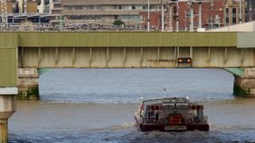 London water bus sails under Cannon Street Bridge stock video