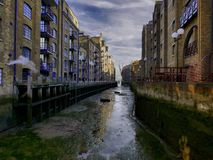A London wharf. Old canal linking South London with the Thames and old warehouse refurbished Royalty Free Stock Images