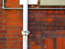 London white pipe and steel tube on a weathered brick wall. Brick wall patina and plumbing pipe painted white. Another galvanized steel tube to protect an stock image