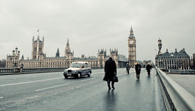 London in Winter. Pedestrians cross Parliament Bridge in snowy conditions which paralyzed London and the rest of England during the winter of 2010 Royalty Free Stock Photos