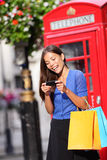 London woman on smart phone shopping. Texting on mobile phone holding shopping bags by red phone booth. Female shopper smiling in London, England, United Royalty Free Stock Photo