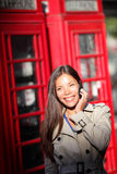 London woman on smartphone by red phone booth. London woman taking on smartphone by red phone booth. Young casual female business woman having conversation on Royalty Free Stock Photography
