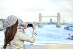 London woman tourist taking photo on Tower Bridge. With mobile smart phone camera. Girl enjoying view over the River Thames, London, England, Great Britain Stock Photo