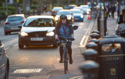 Londoners commuting from work by bike. Road view with cars and bikers. LONDON, UK - 7 SEPTEMBER, 2015: Londoners commuting from work by bike. Road view with cars Stock Photography