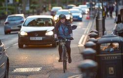 Londoners som pendlar från arbete med cykeln Vägsikt med bilar och cyklister Arkivbild