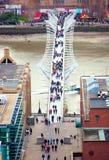 LondonMillennium在通过走泰晤士河和办公室的人民的脚桥梁 免版税库存照片