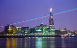 Londra, Inghilterra - luce laser attraverso il cielo notturno di Londra con il grattacielo del coccio Fotografie Stock