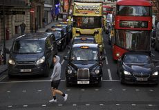 Londra, Inghilterra: 8 marzo 2018: Persona che cammina davanti ad una carrozza nera e ad altre automobili fotografie stock libere da diritti