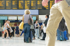 Londra, Inghilterra, Regno Unito - 31 agosto 2016: La donna controlla i bordi di partenza del treno Immagini Stock Libere da Diritti