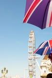 Londra, Regno Unito - 30 agosto 2016: Occhio di Londra nei precedenti degli ombrelli de-messi a fuoco con la bandiera dell'Inghil Immagini Stock Libere da Diritti