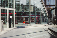 LONDRA, Regno Unito - 14 aprile 2015: giovane donna di affari che cammina lungo la strada con traffico ed i bus rossi su fondo Fotografia Stock