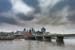 LONDRA, REGNO UNITO - 9 APRILE 2013: Il Tamigi con il traghetto ed il centro di affari nel fondo giorno nuvoloso Fotografia Stock Libera da Diritti