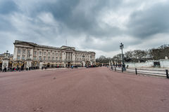 LONDRA, REGNO UNITO - 9 APRILE 2013: Trafalgal quadra il palazzo con il cielo nuvoloso e molti turisti Fotografia Stock Libera da Diritti