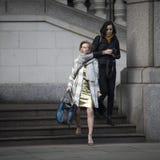 Londra, Regno Unito - 22 dicembre 2017: Una donna in un vestito dall'oro si siede su un banco di pietra, aspettante il suo amico  Fotografie Stock