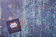 LONDRA, REGNO UNITO - 22 MARZO 2018: Sottobicchiere 1664 del beermat della birra di Kronenbourg su legno blu Fotografia Stock Libera da Diritti