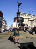 Londra, Regno Unito, 2015-02-23 Musicista scozzese che gioca vicino alla statua di Anteros al circo di Piccadilly fotografia stock