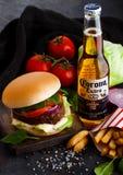 LONDRA, REGNO UNITO - 5 OTTOBRE 2018: Bottiglia di Corona Extra Beer sulla tavola con l'hamburger fresco del manzo e sui chip con immagine stock