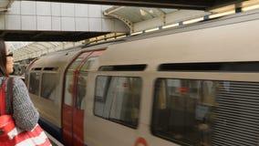Londra, Regno Unito - 20 ottobre 2017: La gente che aspetta al binario sotterraneo del tubo il treno arriva nel undergroun di Ham archivi video