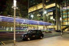 LONDRES, CANARY WHARF Reino Unido - estação 4 de abril de 2014 de Canary Wharf do tubo, do ônibus e do táxi na noite Fotografia de Stock Royalty Free