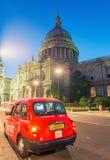 LONDRES - 12 DE JUNIO DE 2015: Taxi rojo debajo del santo Paul Cathedral en el ni Fotos de archivo libres de regalías
