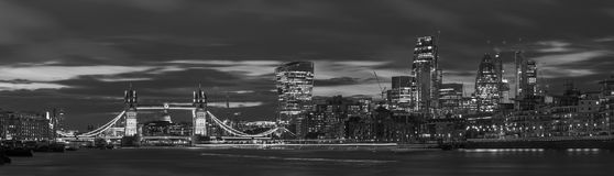 Londres - el panorama del puente, de la orilla y de los rascacielos de la torre en la oscuridad con las nubes dramáticas fotos de archivo libres de regalías