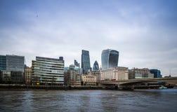 Londres, Inglaterra - autobuses de dos plantas rojos icónicos en el puente de Londres con los edificios de oficinas y los rascaci Foto de archivo libre de regalías
