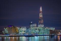 Londres, Inglaterra - ayuntamiento de Londres y oficinas con el rascacielos famoso del casco por noche foto de archivo