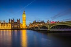 Londres, Inglaterra - Ben Clock Tower grande e casas do parlamento com os ônibus de dois andares vermelhos icônicos na cidade de  Foto de Stock Royalty Free