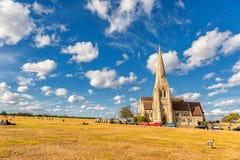 LONDRES, INGLATERRA - 21 DE AGOSTO DE 2016: Blackheath con todos los santos Parque de Greenwich con el cielo azul nublado y la hi Foto de archivo libre de regalías