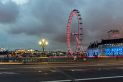LONDRES, INGLATERRA - 16 DE JUNIO DE 2016: Foto de la noche del ojo y del County Hall de Londres del puente de Westminster, Londr Fotografía de archivo