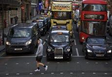 Londres, Inglaterra: 8 de março de 2018: Pessoa que anda na frente de um táxi preto e de outros carros fotos de stock royalty free