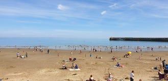 Londres, Inglaterra, Folkestone, kent: 1? de junho de 2019: Os turistas em areias ensolaradas encalham a aprecia??o da luz do sol fotografia de stock