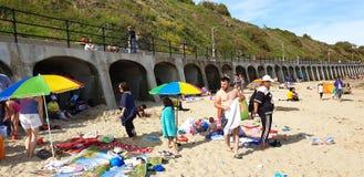 Londres, Inglaterra, Folkestone, kent: 1? de junho de 2019: Os turistas em areias ensolaradas encalham a aprecia??o da luz do sol fotos de stock