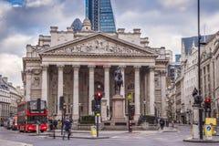 Londres, Inglaterra - ônibus vermelho icônico do ônibus de dois andares e a construção de troca real Foto de Stock Royalty Free