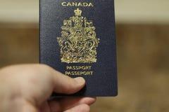 Londres Ontario Canadá - 14 de abril de 2018: Hombre que sostiene un pasaporte canadiense aislado El pasaporte canadiense es uno  imágenes de archivo libres de regalías