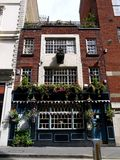 Londres: pub viejo con las cestas de la flor Foto de archivo libre de regalías