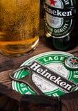 LONDRES, R-U - 10 AOÛT 2018 : Caboteur de bière de Heineken avec le dessus de bouteille et l'ouvreur et le verre de bière sur le  photos stock