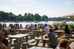 Londres, R-U Les gens ayant un casse-croûte par le lac serpentin dans le Hyde Park photographie stock libre de droits