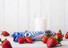 LONDRES, R-U - 3 MAI 2018 : Biscuits originaux de fraise d'Oreo avec les baies et le verre frais de lait Photos libres de droits