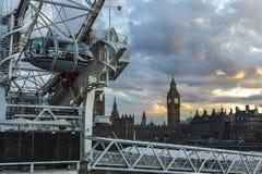 LONDRES, REINO UNIDO - 2016 04 05: Big Ben y la puesta del sol del ojo de Londres Fotos de archivo libres de regalías