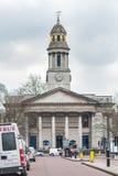 LONDRES, REINO UNIDO - 9 DE ABRIL DE 2013: Architeture bulding con el reloj y los coches que parquean en el steeet Ningunas perso Foto de archivo libre de regalías